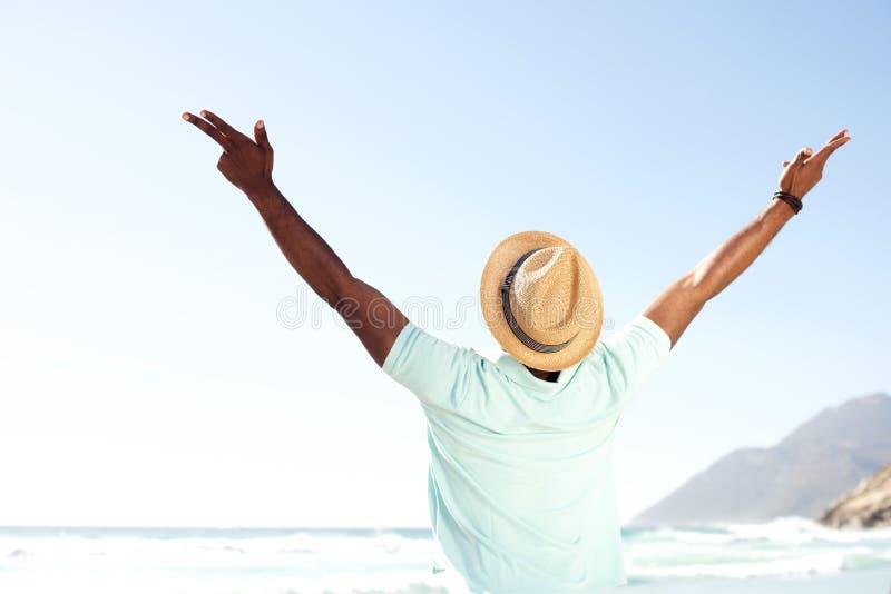 Hombre joven que se coloca con la extensión de los brazos abierta en la playa imagenes de archivo