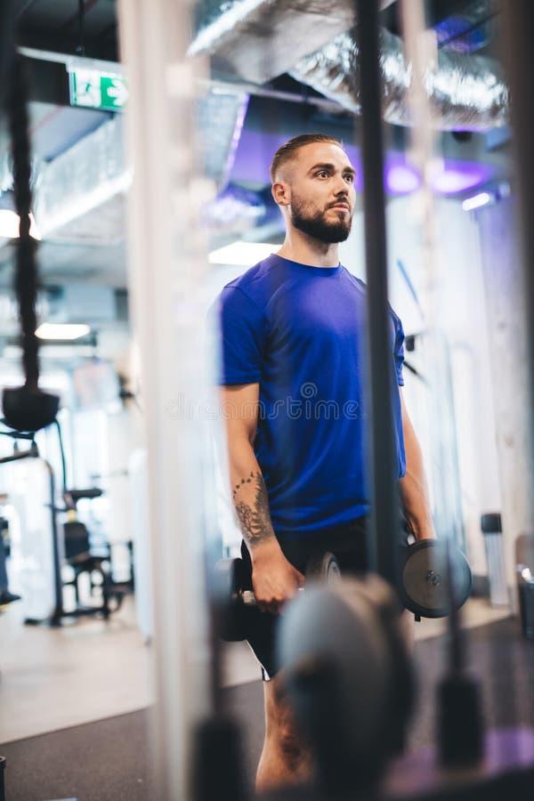 Hombre joven que se coloca con pesas de gimnasia en el gimnasio imagenes de archivo