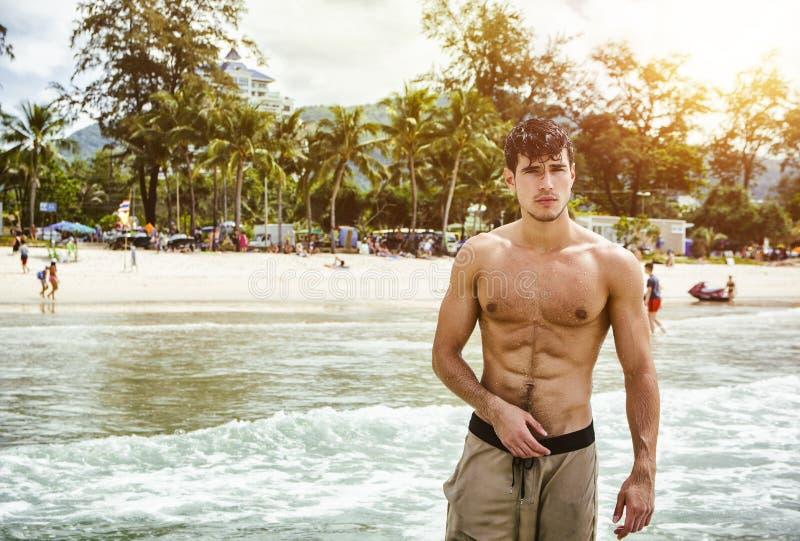 Hombre joven que se coloca en el borde del océano imagen de archivo libre de regalías