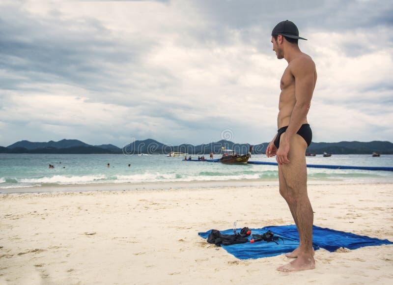 Hombre joven que se coloca en el borde del océano fotos de archivo libres de regalías
