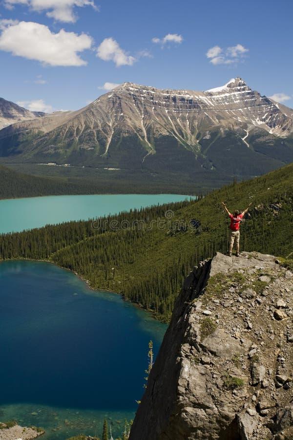 Hombre joven que se coloca en el canto rodado sobre los lagos imagenes de archivo