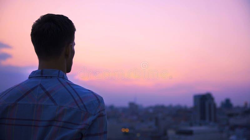 Hombre joven que se coloca en el tejado de la construcción solamente y de meditar, disfrutando de la libertad imágenes de archivo libres de regalías