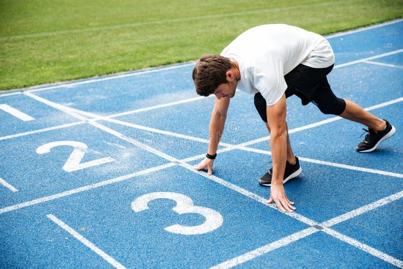 Hombre joven que se coloca en la posición de salida para correr respecto a pista imagenes de archivo