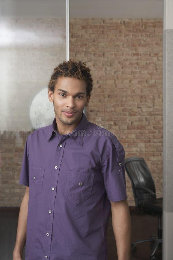 Hombre joven que se coloca en oficina imagenes de archivo