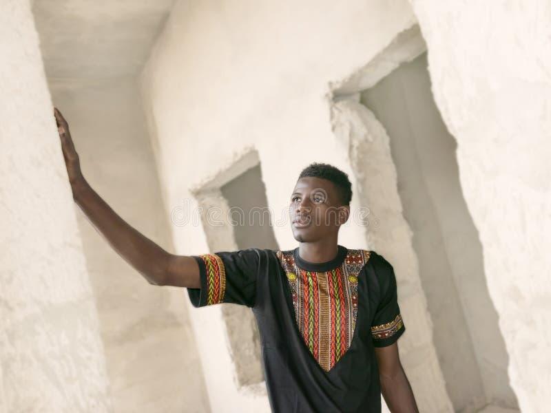 Hombre joven que se coloca en un edificio inacabado imagen de archivo libre de regalías