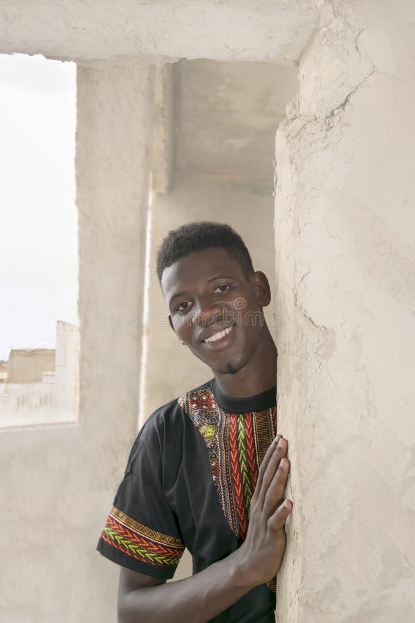 Hombre joven que se coloca en un edificio inacabado foto de archivo