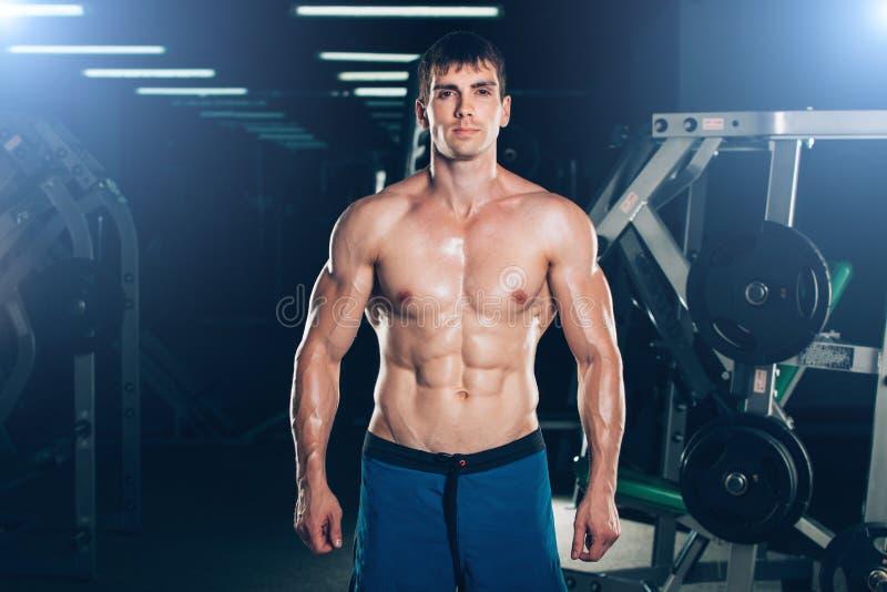 Hombre joven que se coloca fuerte en el gimnasio y que dobla los músculos - modelo atlético muscular Posing After de la aptitud d foto de archivo libre de regalías