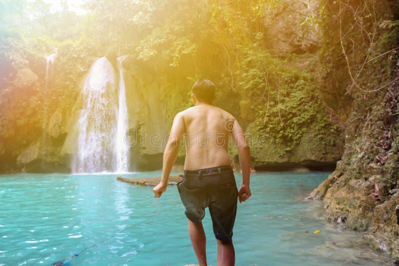 Hombre joven que se mueve adelante para saltar de la charca en escena de la cascada imagen de archivo