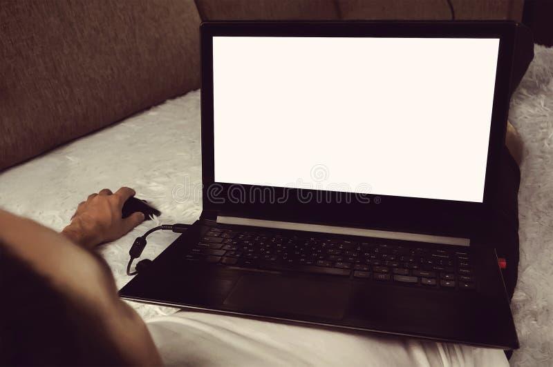 Hombre joven que se relaja en el sofá con un ordenador portátil imágenes de archivo libres de regalías