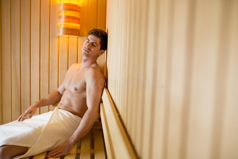 Hombre joven que se relaja en la sauna fotografía de archivo