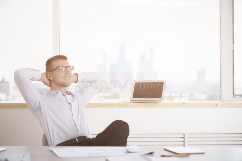Hombre joven que se relaja en oficina foto de archivo libre de regalías