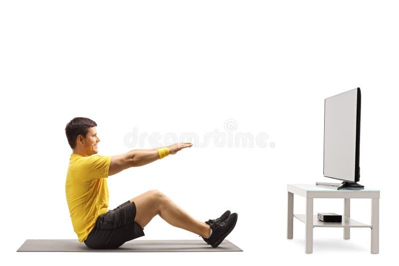 Hombre joven que se resuelve delante de una TV imágenes de archivo libres de regalías