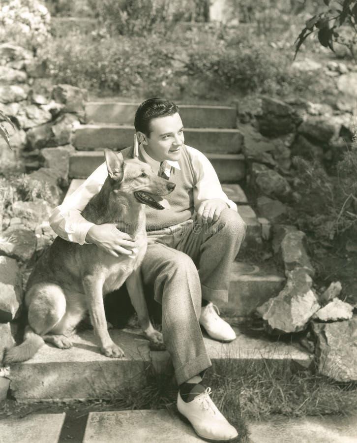 Hombre joven que se sienta con el perro en pasos al aire libre foto de archivo libre de regalías