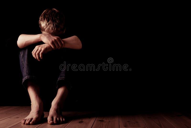 Hombre joven que se sienta con los brazos sobre rodillas foto de archivo libre de regalías