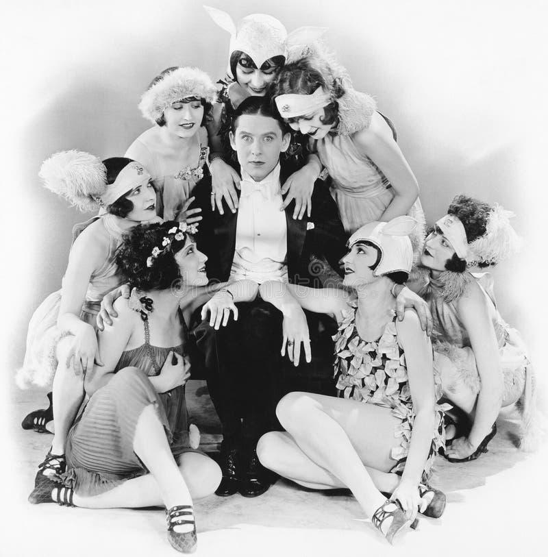 Hombre joven que se sienta con un grupo de mujeres jovenes alrededor de él (todas las personas representadas no son vivas más lar fotos de archivo