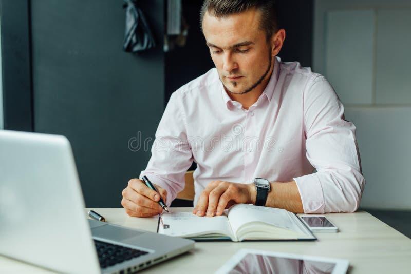 Hombre joven que se sienta en café y que añade la nueva reunión en su calenda fotografía de archivo libre de regalías