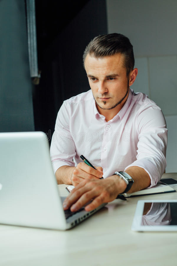 Hombre joven que se sienta en café y que añade la nueva reunión en su calenda foto de archivo libre de regalías