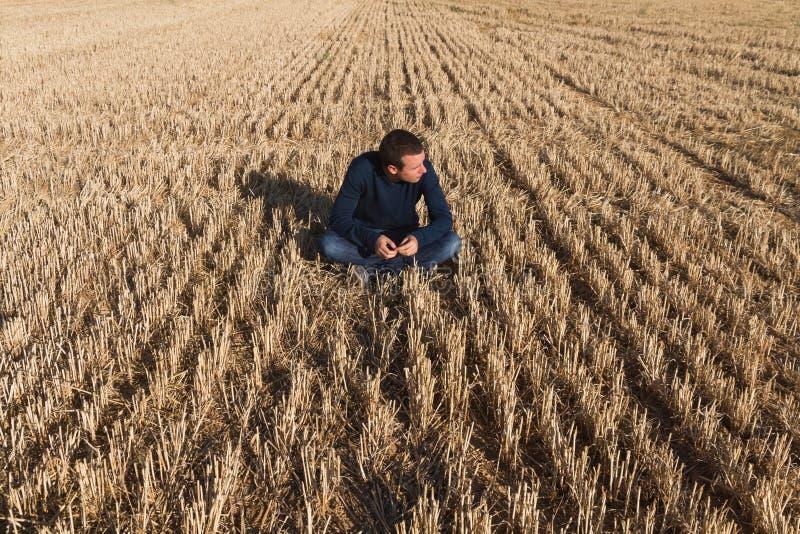 Download Hombre Joven Que Se Sienta En Campo Imagen de archivo - Imagen de outdoor, suelo: 41911375