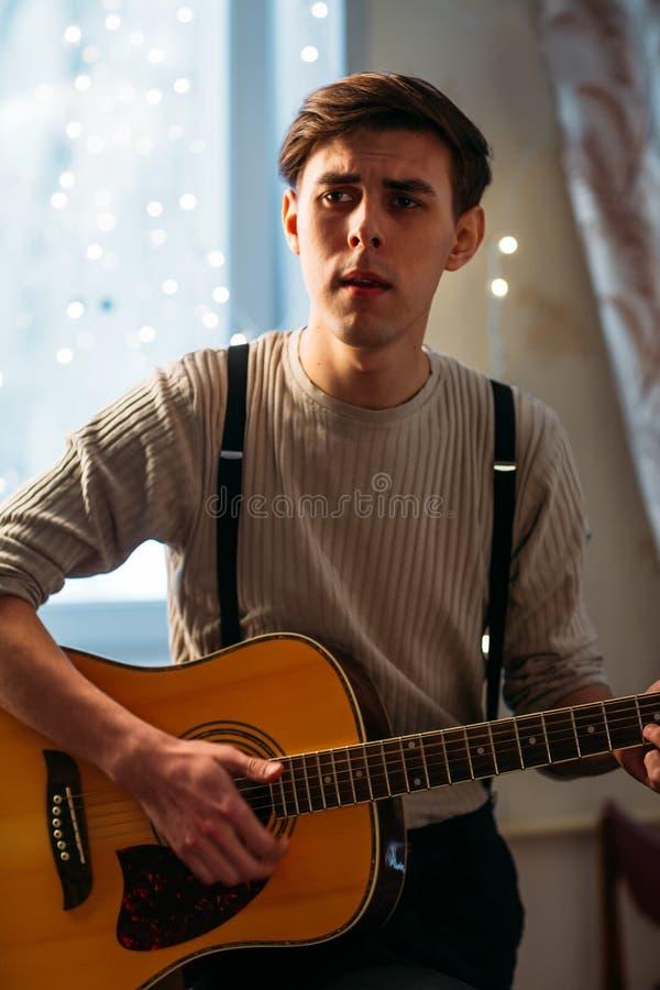 Hombre joven que se sienta en casa y que toca la guitarra dramática imagenes de archivo