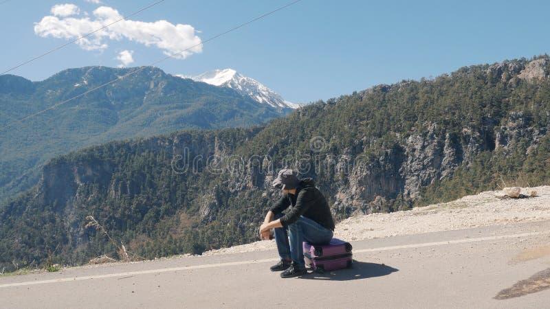 Hombre joven que se sienta en día soleado púrpura de la maleta imagenes de archivo