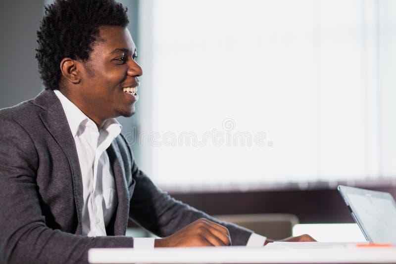 Hombre joven que se sienta en el escritorio, concepto del negocio, educación, oficinista fotografía de archivo