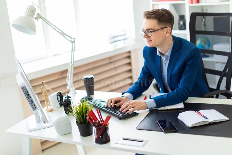Hombre joven que se sienta en el escritorio en oficina y que trabaja en el ordenador imágenes de archivo libres de regalías