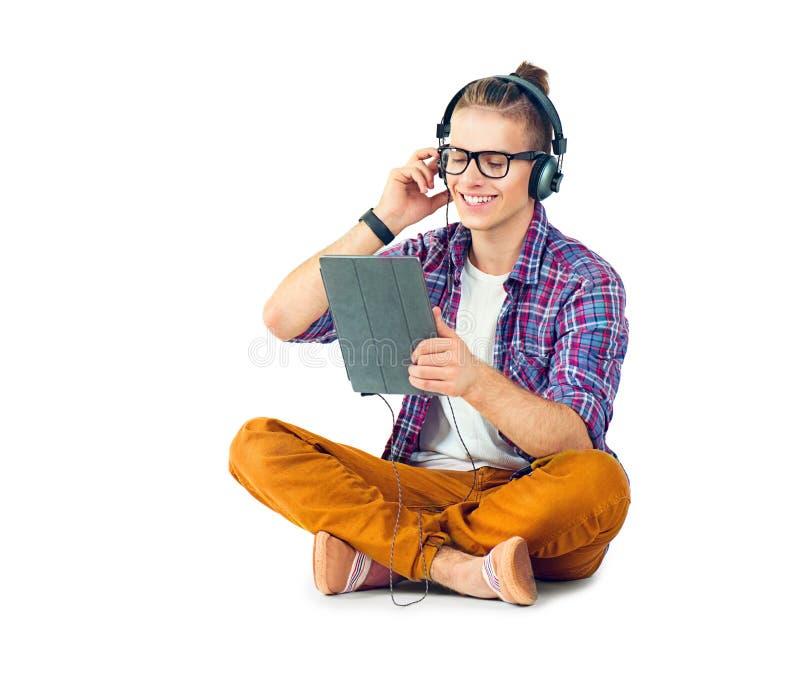 Hombre joven que se sienta en el piso y que disfruta de música fotos de archivo libres de regalías