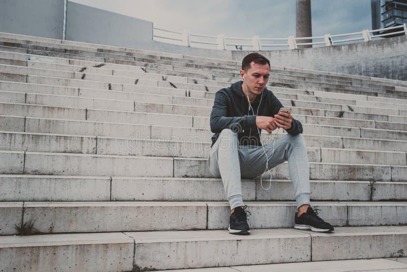 Hombre joven que se sienta en el puente moderno en la ciudad, usando su smartphone imágenes de archivo libres de regalías
