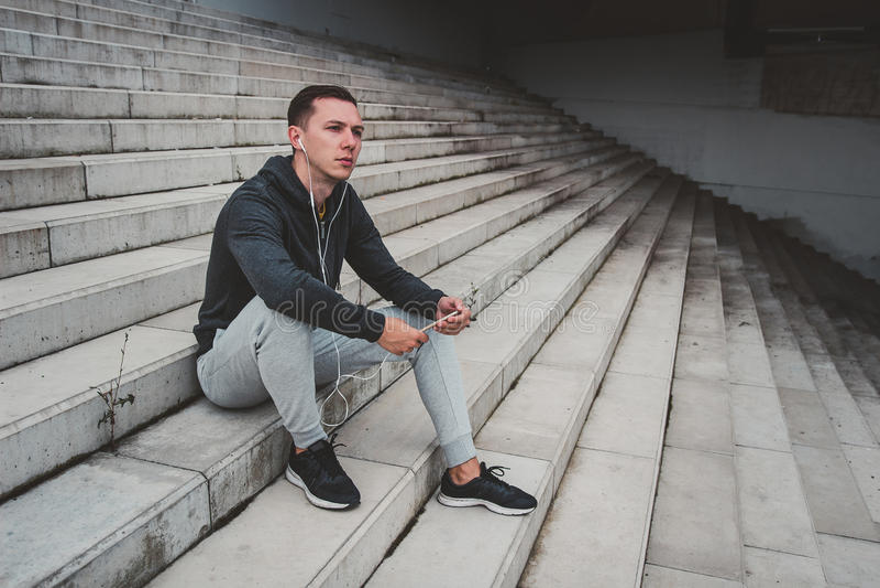 Hombre joven que se sienta en el puente moderno en la ciudad, usando su smartphone fotografía de archivo libre de regalías