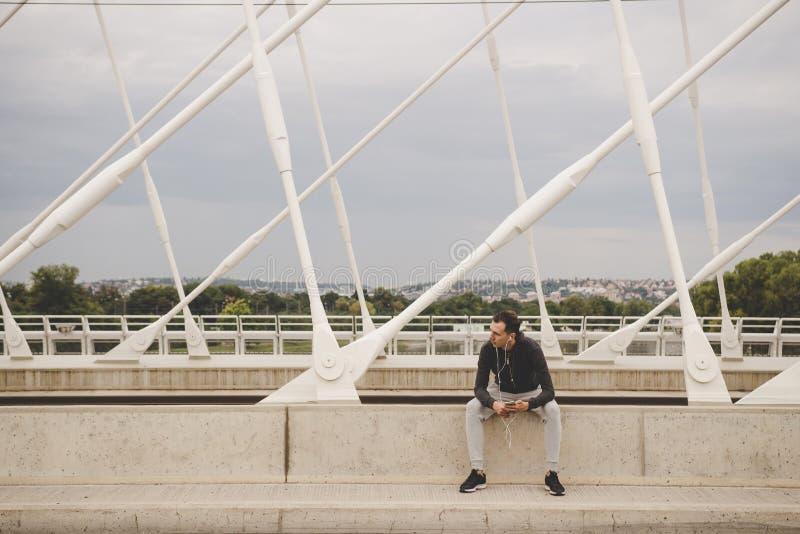 Hombre joven que se sienta en el puente moderno en la ciudad, usando su smartphone imagen de archivo libre de regalías