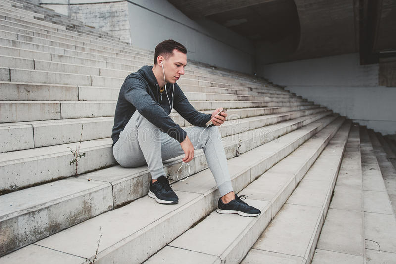 Hombre joven que se sienta en el puente moderno en la ciudad, usando su smartphone fotografía de archivo
