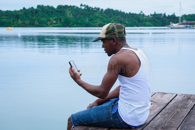 Hombre joven que se sienta en el puerto deportivo y que mira su smartphone que toma selfies imagen de archivo