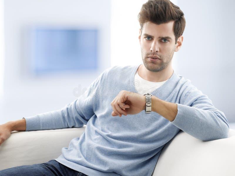 Hombre joven que se sienta en el sofá en casa fotos de archivo