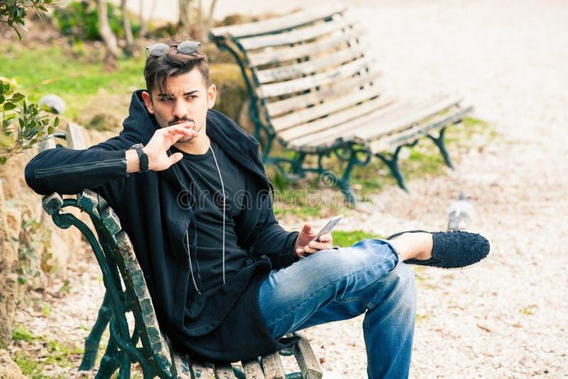 Hombre joven que se sienta en esperar de pensamiento del banco con el teléfono a disposición fotografía de archivo