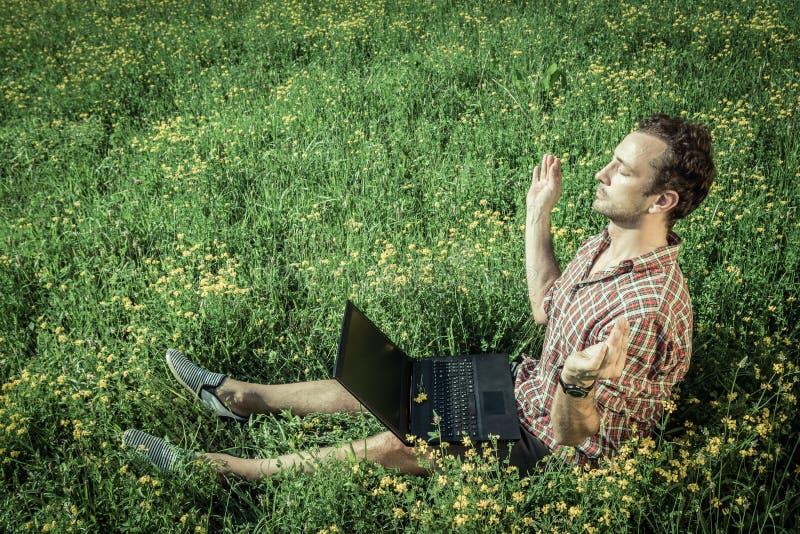 Hombre joven que se sienta en la hierba y meditar Ordenador portátil en su kne foto de archivo