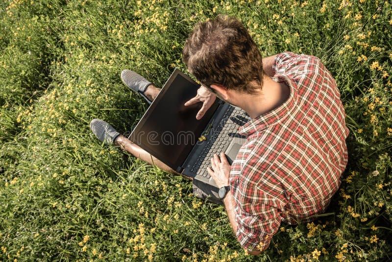 Hombre joven que se sienta en la hierba y que muestra en la pantalla del ordenador portátil con foto de archivo libre de regalías