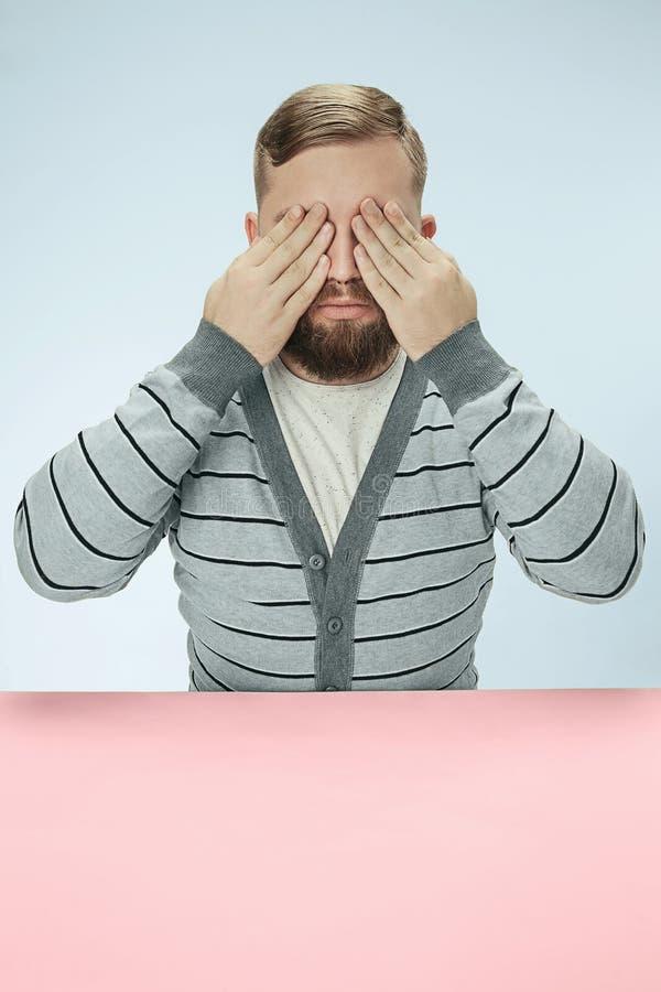 Hombre joven que se sienta en la tabla en el estudio con los ojos cerrados en azul imágenes de archivo libres de regalías