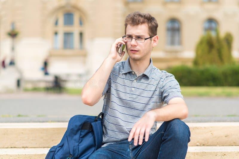 Hombre joven que se sienta en las escaleras con su teléfono imagen de archivo libre de regalías