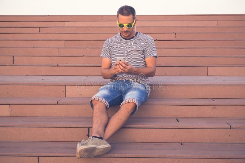 Hombre joven que se sienta en las escaleras y que usa smartphone fotografía de archivo