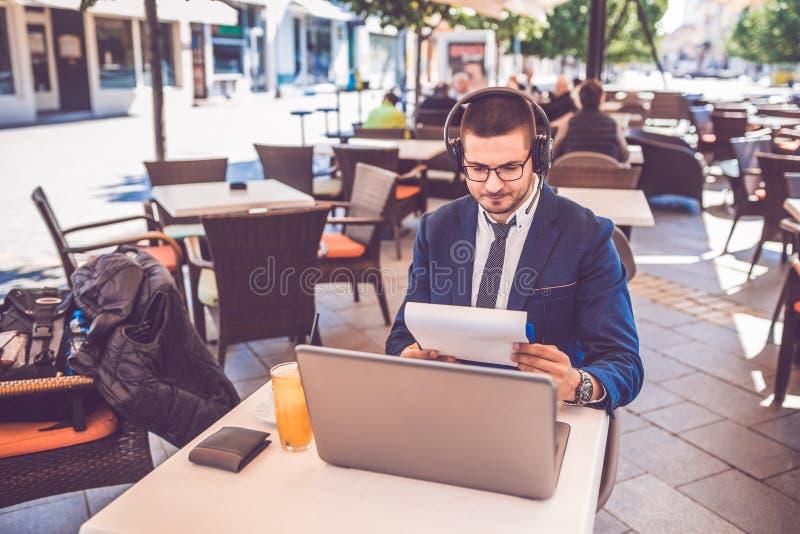 Hombre joven que se sienta en los documentos de la lectura del café de la calle mientras que trabaja en el ordenador portátil y l imagen de archivo