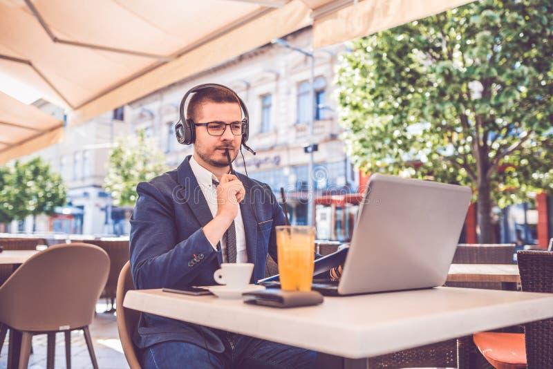 Hombre joven que se sienta en los documentos de la lectura del café mientras que trabaja en el ordenador portátil y los auricular imagen de archivo