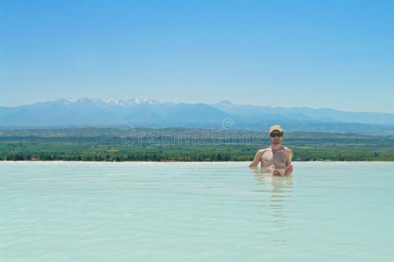 Hombre joven que se sienta en piscina termal con Mountain View fotografía de archivo