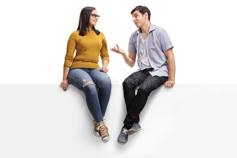 Hombre joven que se sienta en un letrero en blanco y que habla con una mujer joven foto de archivo libre de regalías