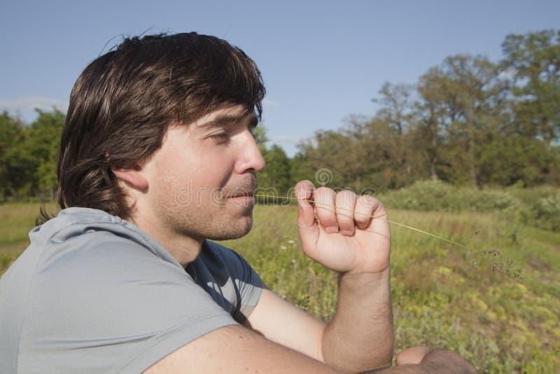 Hombre joven que se sienta en un prado fotos de archivo libres de regalías