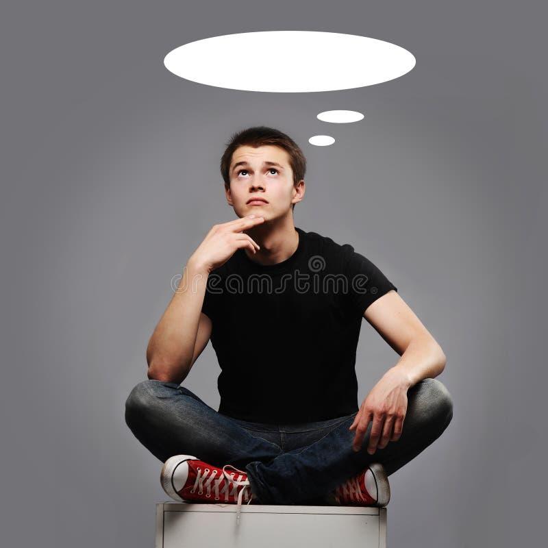 Hombre joven que se sienta y que piensa en algo fotos de archivo libres de regalías