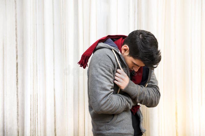 Hombre joven que siente suéter pesado muy frío, que lleva foto de archivo