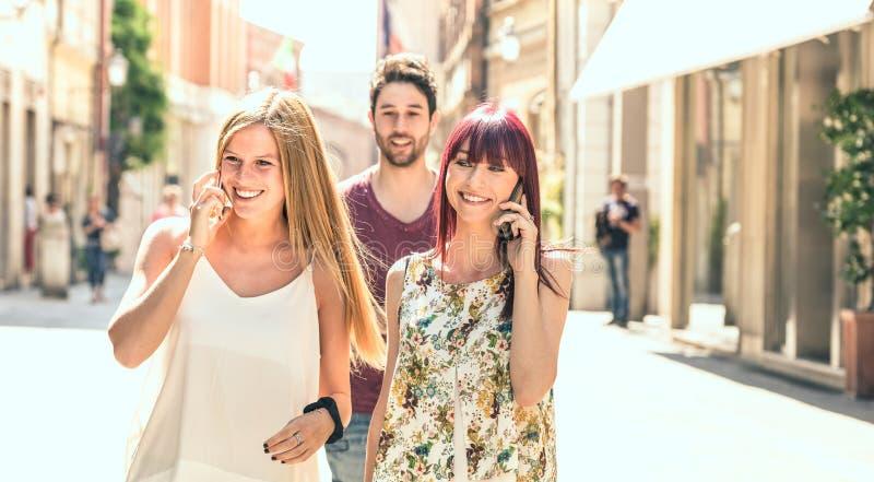 Hombre joven que sigue a mujeres bonitas mientras que divirtiéndose junto en la calle de la ciudad - concepto de la tecnología en imagen de archivo