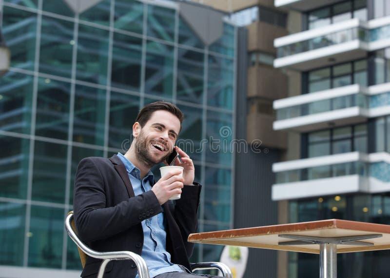 Hombre joven que sonríe con el teléfono móvil imágenes de archivo libres de regalías