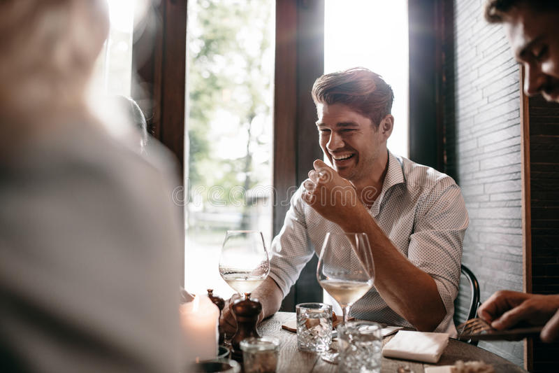 Hombre joven que sonríe con los amigos en el restaurante imagen de archivo libre de regalías