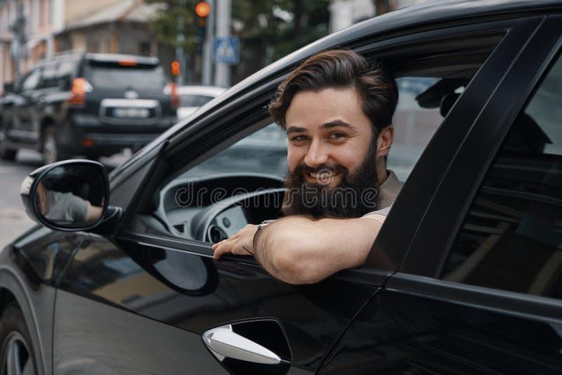 Hombre joven que sonríe mientras que conduce un coche imagen de archivo